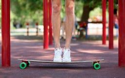Primer de las piernas masculinas en un fondo natural Un individuo juguetón que se coloca en su longboard Deporte, al aire libre c Imagen de archivo