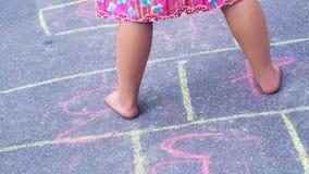 Primer de las piernas y de las rayuelas del ` s del niño pequeño dibujado en el asfalto Niño que juega a la rayuela el juego en p imagenes de archivo