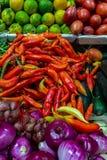 Primer de las pimientas de chile rojo en una parada del mercado en medio de otras verduras fotos de archivo