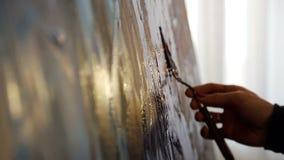 Primer de las pinturas del artista con las pinturas acrílicas en la luz de oro caliente Movimiento lento de la c?mara Dibujo con  almacen de metraje de vídeo