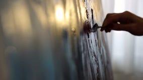 Primer de las pinturas del artista con las pinturas acr?licas en la luz de oro caliente Movimiento lento de la c?mara Dibujo con  almacen de metraje de vídeo