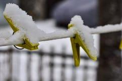 Primer de las pinzas para la ropa que se lava, atadas a una cuerda nevada contra el cielo azul y el sol brillante fotografía de archivo libre de regalías