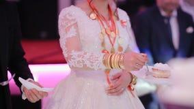 Primer de las pulseras grandes y del collar del oro femenino hermoso de las manos, probando el pastel de bodas Joyería turca del  metrajes
