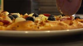 Primer de las rebanadas del cocinero de pizza en una placa almacen de video