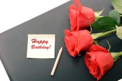 Primer de las rosas rojas en un ordenador portátil Tarjeta del feliz cumpleaños Fotografía de archivo