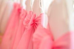 Primer de las sillas blancas de la boda con la cinta rosada Fotos de archivo