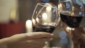 Primer de los amigos que tintinean los vidrios del vino tinto y del champ?n en el restaurante acci?n Reuni?n del ` s del amigo almacen de video