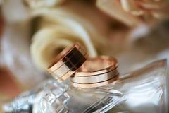 Primer de los anillos de bodas en el fondo de las rosas y del vidrio, accesorios de la boda fotos de archivo