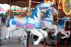 Primer de los caballos del carrusel en la feria de condado Fotografía de archivo libre de regalías