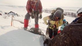 Primer de los escaladores que ajustan el equipo gente que lleva la ropa caliente, equipo, ella se está preparando para la pendien metrajes