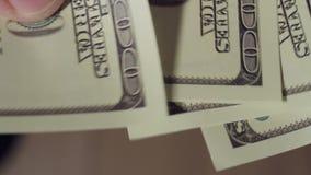 Primer de los fingeres que mueven de un tirón 100 billetes de dólar metrajes