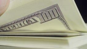 Primer de los fingeres que mueven de un tirón 100 billetes de dólar almacen de metraje de vídeo
