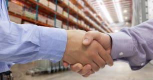 Primer de los hombres de negocios que sacuden las manos en almacén Foto de archivo