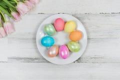 Primer de los huevos de Pascua coloreados en el fondo de madera apenado blanco fotos de archivo