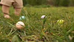 Primer de los huevos de Pascua en la hierba contra la perspectiva de los pies de un niño que recoge los huevos Caza del huevo de  almacen de video