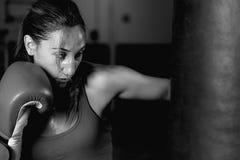 Primer de los movimientos practicantes profesionales del atleta de sexo femenino en el saco de arena imagen de archivo libre de regalías