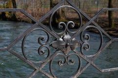 Primer de los ornamentos negros del hierro de una barandilla del ` s del puente fotos de archivo