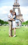 Primer de los pares felices que abrazan cerca de la torre Eiffel Imagen de archivo