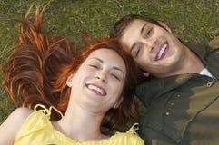 Primer de los pares felices que mienten en hierba Fotografía de archivo