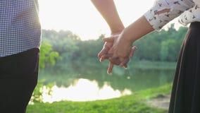 Primer de los pares que llevan a cabo las manos en la puesta del sol y que caminan junto metrajes