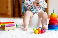 Primer de los pequeños 12 meses lindos del niño del niño del bebé que se sienta en el potty fotografía de archivo