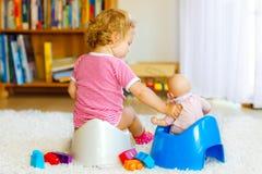 Primer de los pequeños 12 meses lindos del niño del niño del bebé que se sienta en el potty Niño que juega con el juguete de la m imagen de archivo libre de regalías