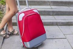 Primer de los pies de una chica joven cerca de la maleta roja del viaje outdoors Imagenes de archivo