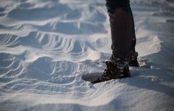 Primer de los pies del ` s de la mujer que caminan en el desierto de la nieve en la puesta del sol Tiro de la cámara lenta de Sta Imagenes de archivo