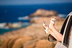 Primer de los pies femeninos que muestran de paisaje hermoso del fondo de la ventanilla del coche Fotos de archivo