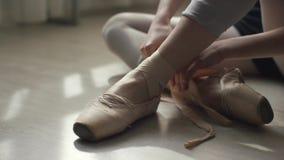 Primer de los pies de la bailarina en un piso de madera ligero Muchacha que ata la cinta de los zapatos del pointe metrajes