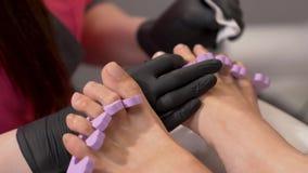 Primer de los pies de la mujer con los separadores del dedo del pie Limpiando las uñas del pie antes de aplicar el pulimento almacen de video