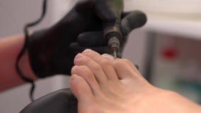 Primer de los pies de la mujer Quitando las cutículas y el clavo de la uña del pie que pulen con pedicura de los pies perfore la  almacen de video