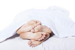 Primer de los pies que abrazan en cama Foto de archivo