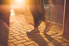 Primer de los pies de una señora joven en la puesta del sol imagenes de archivo