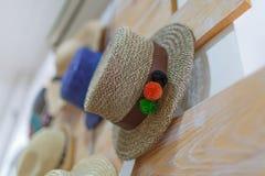 Primer de los sombreros bonitos de las mujeres Sombreros clásicos del verano que cuelgan en una tienda en un fondo de la pared Ac Fotos de archivo libres de regalías