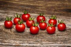 Primer de los tomates de cereza frescos, maduros en la madera Foto de archivo libre de regalías