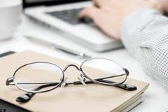 Primer de los vidrios del ojo con un hombre de negocios que trabaja en el ordenador portátil fotografía de archivo