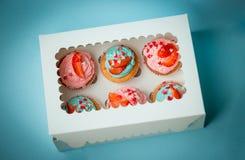 Primer de magdalenas coloridas con la fresa en la caja de papel sobre b Fotos de archivo libres de regalías