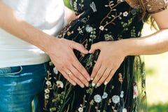 Primer de manos cariñosas en la forma de un corazón El marido y la esposa conectan sus manos contra la perspectiva de a fotografía de archivo