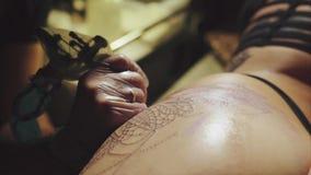 Primer de manos del artista del tatuaje en los guantes que tatúan un modelo en macro del cuerpo almacen de metraje de vídeo