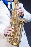 Primer de manos del jugador de saxofón de sexo masculino que presenta con el saxofón Imagen de archivo libre de regalías