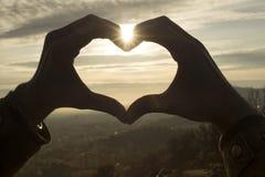 Primer de manos en forma de corazón en el cielo de la puesta del sol imagen de archivo libre de regalías