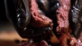 Primer de manos en los guantes de goma negros que llevan a cabo pedazos tajados de carne guisada almacen de video