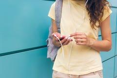 Primer de manos femeninas con la manicura blanca que sostiene el móvil rosado Fotos de archivo libres de regalías