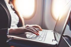 Primer de manos femeninas usando el ordenador portátil Funcionamiento de la mujer mientras que va en viaje de negocios en avión fotografía de archivo