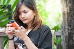 Primer de manos femeninas usando el teléfono elegante moderno mientras que trabaja, Imagen de archivo