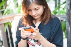 Primer de manos femeninas usando el teléfono elegante moderno mientras que trabaja, Fotos de archivo libres de regalías