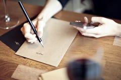 Primer de manos, funcionamiento, escritura en un restaurante Concepto del asunto Disposiciones inmóviles Fotos de archivo