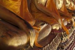 Primer de manos de la fila de las estatuas de oro asentadas de Buda en claustros fotografía de archivo