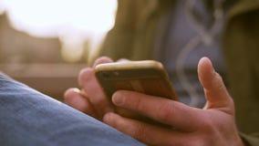 Primer de manos para hombre con el teléfono con la tarjeta de crédito en mandar un SMS trasero almacen de metraje de vídeo